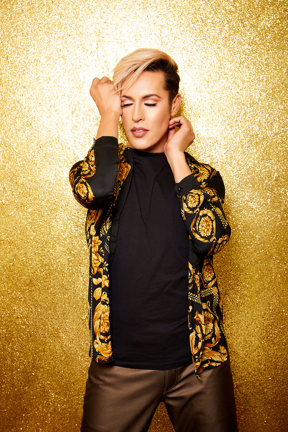 Dario wearing gold embroidered jacket, standing in front of golden glitter with hands up to face