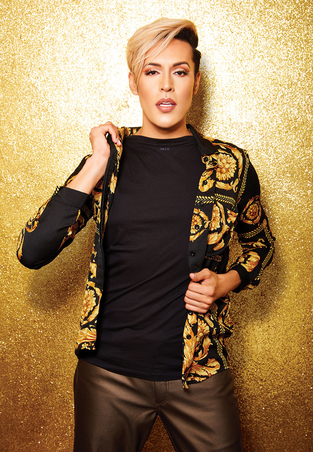 Dario standing in front of golden glitter, spreading his gold embroidered jacket with his hands
